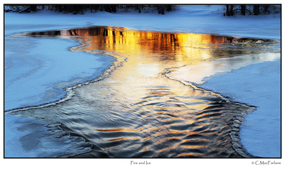Frozen and open water, reflecting winter sunset.